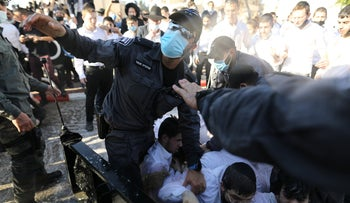 Protesters clash with police as they attempt to close down a school open against coronavirus lockdown violations, Ashdod, January 11, 2021.