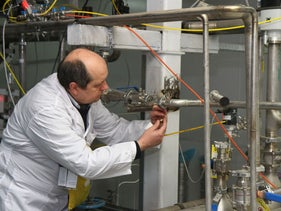An unidentified International Atomic Energy Agency (IAEA) inspector disconnects the connections between the twin cascades for 20 percent uranium production at nuclear power plant of Natanz, Iran, January 20, 2014.