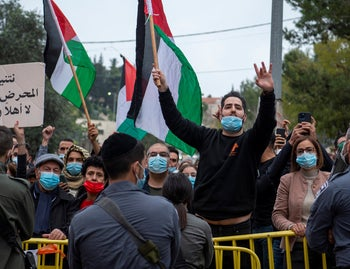 A man gives a rude gesture at a protest against Netanyahu's visit to Nazareth, January 13, 2021.