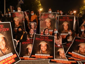 Teen girls clutch posters with the face of Ahuvia Sandak, who was killed in a police chase, January 2, 2021.