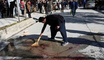 A resident washes a road following gunmen shot dead two Afghan women judges working for the Supreme Court, in Kabul on January 17, 2021