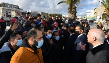 In this photo provided by the Tunisian presidency, President Kais Saied, right, meets residents in Mnihla, outside Tunis, during a wave of renewed anti-government protests, January 18, 2021.