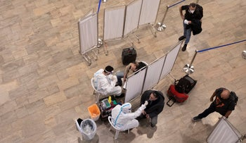 Health workers test passengers for the coronavirus at Ben-Gurion Airport, Israel's main international airport, in January 2021.