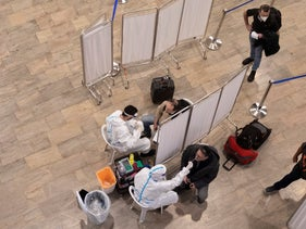 Healthworkers test passengers arriving at Ben Gurion Airport, Israel's main airport, for coronavirus, January 2021.
