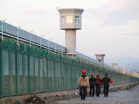 Workers walk by the perimeter fence of what is officially known as a vocational skills education centre in Dabancheng in Xinjiang Uighur Autonomous Region, China September 4, 2018