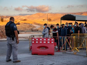 Palestinian laborers line up to cross a checkpoint at the entrance to the Israeli settlement of Ma'aleh Adumim, near Jerusalem, June 30, 2020