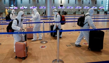 Passengers wearing full protective suits and masks push their luggage trolleys at the departures area at Ben-Gurion International Airport, January 19, 2021.