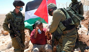 Israeli soldiers remove Palestinian landowners and demonstrators protesting settlement construction on their land in al-Thaalaba village, south of Hebron in the West Bank, August 21, 2020.