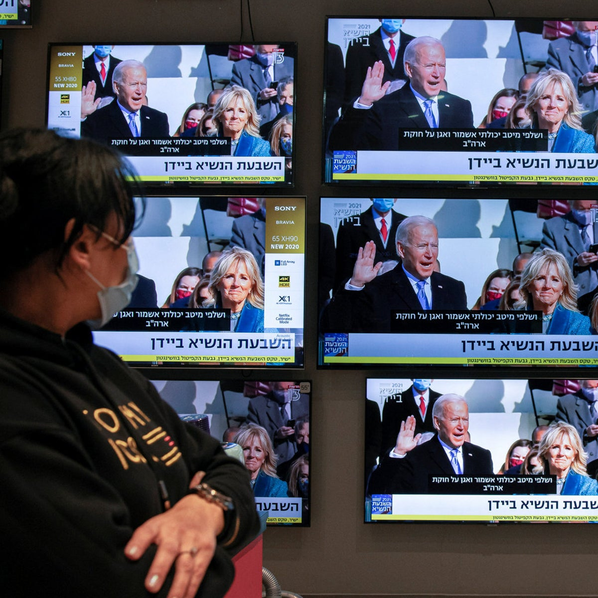 An Israeli electronics store employee looks at a wall of televisions broadcasting live the 59th U.S. Presidential Inauguration ceremony, in Ashkelon, Israel, January 20, 2021.