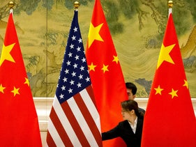 Chinese staffers adjust U.S. and Chinese flags before the opening session of Sino-U.S. trade negotiations in Beijing, February 14, 2019.