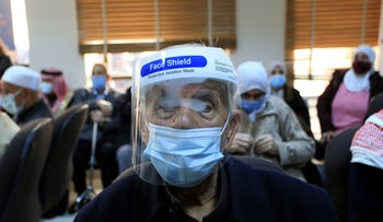People wait to receive a Pfizer vaccine at a vaccination center, in Amman, January 13, 2021.