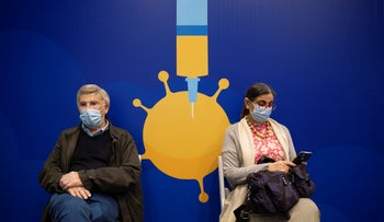 People rest after receiving coronavirus vaccines at a COVID-19 vaccination center in Tel Aviv, January 3, 2021.