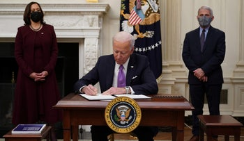 US President Joe Biden signs executive orders as part of the Covid-19 response as US Vice President Kamala Harris (L) and Director of NIAID Anthony Fauci look on in the State Dining Room of the White House in Washington, DC, on January 21, 2021