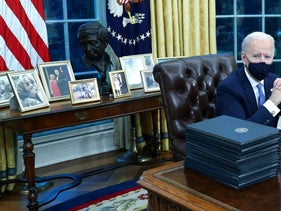 Biden family photos are displayed around a bust of activist Cesar Chavez, as U.S. President Joe Biden prepares to sign executive orders at the Resolute Desk inside the Oval Office of the White House in Washington, U.S., January 20, 2021. Picture taken January 20, 2021