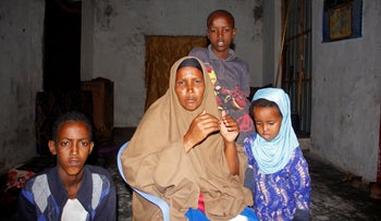 Fadumo Moalim Abdulle poses with 3 of her children, during an interview with the Associated Press in Mogadishu, Somalia, Jan, 18, 2021