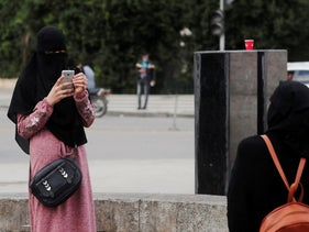 Egyptian women wearing a full veil (niqab) take pictures amid the coronavirus pandemic on Qasr el-Nil bridge, leading to Cairo's Tahrir Square, December 17, 2020.