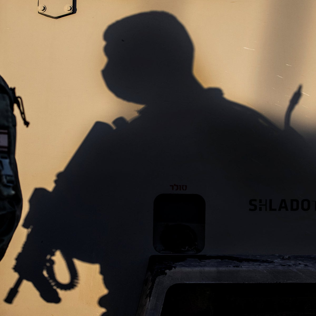The shadow of an Israeli soldier wearing a face mask to help protect against the coronavirus, is cast onto the side of a vehicle, Jan. 21, 2021.