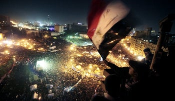 People wave flags in Tahrir Square to mark the first anniversary of the popular uprising that led to the quick ouster of autocrat Mubarak, in Cairo, Egypt, January 25, 2012.