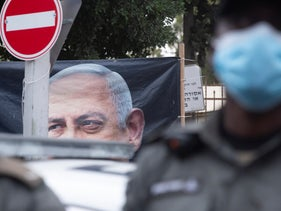 Police stand guard as Israeli anti-government protesters chant slogans outside of the official residence of Prime Minister Benjamin Netanyahu, Jan. 13, 2021.
