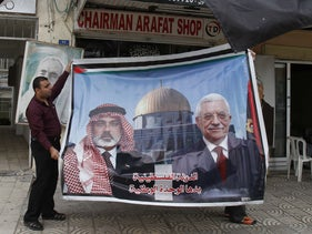 A Palestinian shopkeeper displays a poster of  Hamas leader Ismail Haniyeh and Palestinian President Mahmoud Abbas on reports of a reconciliation agreement. Gaza City, April 28, 2011