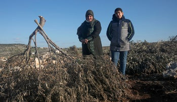 Khatam Dar Musa, from the West Bank village of Dir Blut, with her son, near trees that she had planted that were uprooted.
