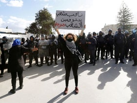 A demonstrator holds up a sign during an anti-government protest in Tunis, Tunisia January 26, 2021