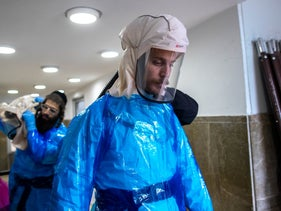 Volunteers from a hevra kadisha, or religious burial society, in full protective gear as they perform Jewish funeral rites for those who have died from COVID-19, Jerusalem, January 25, 2021.