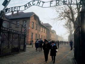 "Holocaust survivors walk below the gate with its inscription ""Work sets you free"" at former death camp Auschwitz to commemorate the 75th anniversary of the camp's liberation in Oswiecim, Poland, January 27, 2020."