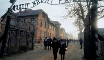 """Holocaust survivors walk below the gate with its inscription """"Work sets you free"""" at former death camp Auschwitz to commemorate the 75th anniversary of the camp's liberation in Oswiecim, Poland, January 27, 2020."""
