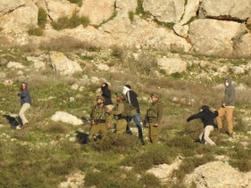 Settlers throwing stones at the Palestinian village of Burin, near Nablus, as Israeli soldiers stand by, January 23, 2021.
