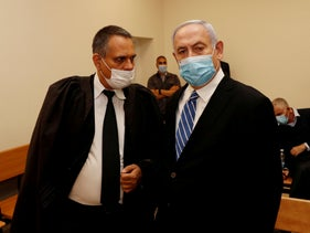Israeli Prime Minister Benjamin Netanyahu, wearing a mask, stands inside the courtroom as his corruption trial opens at the Jerusalem District Court May 24, 2020