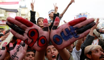 An anti-government protester displays a message written on his palms during a sit-in to demand for the ouster of Yemen's President Ali Abdullah Saleh outside Sanaa University, March 30, 2011.