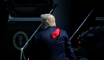 Trump's back. His red tie hangs over the back of his dark jacket.