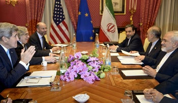 Iranian and U.S. figures, including U.S. Secretary of State John Kerry and Iranian Foreign Minister Javad Zarif, wait to start a meeting at the Beau Rivage Palace Hotel in Lausanne, Switzerland, March 29, 2015.