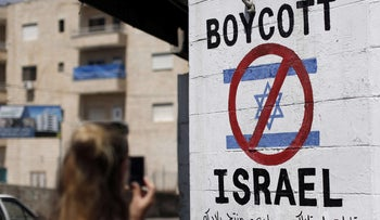 A tourist photographs a sign painted on a wall in the West Bank of Bethlehem on June 5, 2015.
