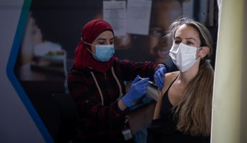 An Israeli receives the COVID-19 vaccine at the Clalit HMO center in Petah Tikva, January 27, 2021.