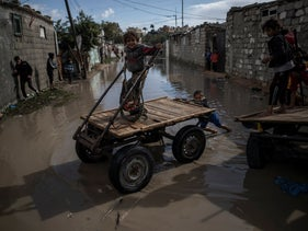 Palestinian children play in a flooded street during a rainy day in a poor neighborhood of Khan Younis, in the southern Gaza Strip, January 20, 2021.
