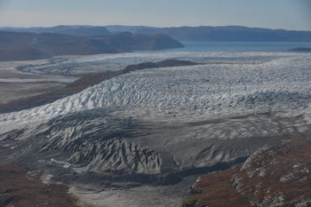 """Disappearing glacier southwest Greenland shown in 2016. Note the dark gray color on top of much of the white ice. This is pulverized rock dust known as cryoconite, produced by the grinding glacier from the bedrock. As the glacier recedes the fierce Arctic winds blow this onto the glacier. The dark color increases the heat absorption and hastens the melting; one of the """"feedback loops"""" in the global warming process"""