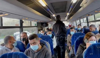 Still from video of policeman fining bus passengers, January 31, 2021.