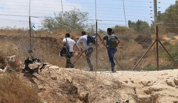 People walk through a hole in a fence that is part of the West Bank separation barrier, August 2020.