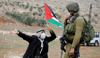 A demonstrator holds a Palestinian flag in front of an Israeli soldier during a protest against Jewish settlements, in Beit Dajan in the Israeli-occupied West Bank November 20, 2020.