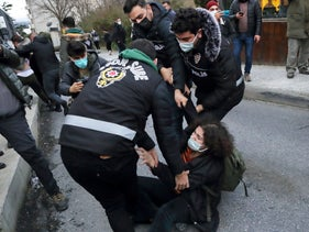 A woman scuffles with police officers as she waits in front of the Bogazici University in solidarity with students inside the campus, Istanbul, Turkey February 1, 2021.