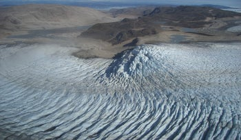 Glacier on west Greenland in August 2007, as it bends in its normal descent to the sea. Due to warming the melting glacier has retreated far inland