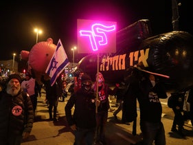 """At a demonstration in Jerusalem on Saturday, a neon sign bears the message """"Go"""" that has become ubiquitous at the anti-Netanyahu protests"""