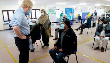 Britain's Prime Minister Boris Johnson (L) speaks to members of the public waiting to receive their vaccine as he visits a coronavirus covid-19 vaccination centre, the Al-Hikmah Vaccination Centre in Batley, northern England