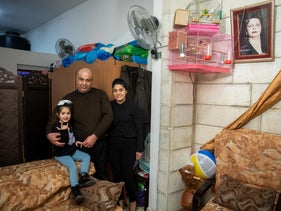 Wasim Masis, his wife Georgette and their daughter Nili in their Beit Hanina apartment, on Monday.