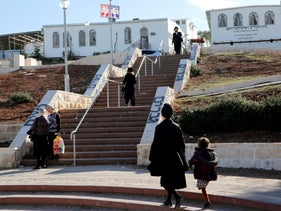 Devout ultra-Orthodox Jews take segregated steps in Beit Shemesh in 2017. The right-side of the flight is for men, the painted sign says, the left for women.