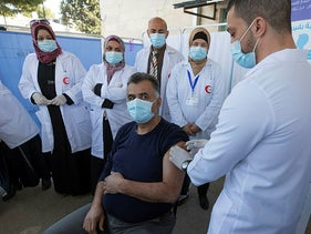 A medic administers a Moderna COVID-19 vaccine to a fellow medic during a campaign to vaccinate front-line medical workers, at the health ministry, in the West Bank city of Bethlehem, Wednesday, Feb. 3, 2021