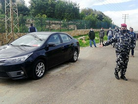 Police gather at a site where Lokman Slim was found killed in a car in southern Lebanon, on Thursday.