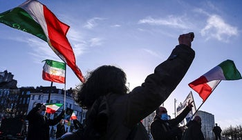 People gesture and wave former flags of Iran as they protest outside the Antwerp criminal court during the trial of four persons including an Iranian diplomate and Belgian-Iranian couple in Antwerp, on Thursday